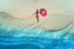 Η εναέρια άποψη της γυναίκας με κολυμπά το δαχτυλίδι στην αμμώδη παραλία στοκ εικόνες