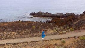 Η εναέρια άποψη της γυναίκας σε ένα όμορφα μπλε φόρεμα και ένα καπέλο περπατά μέσω μιας περιοχής συντήρησης στις ακτές του Ατλαντ απόθεμα βίντεο