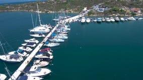 Η εναέρια άποψη της τυρκουάζ θάλασσας με τη μαρίνα γιοτ στον κόλπο Panagia σε Halkidiki Ελλάδα, προωθεί από τον κηφήνα απόθεμα βίντεο