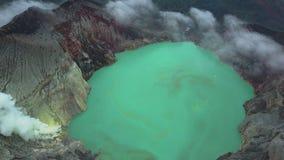 Η εναέρια άποψη του ηφαιστείου Ijen με την όμορφη όξινη λίμνη και το θείο δηλητηριάζουν με αέρια τη μετάβαση από τον κρατήρα φιλμ μικρού μήκους