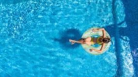 Η εναέρια άποψη του κοριτσιού στην πισίνα άνωθεν, παιδί κολυμπά διογκώσιμο doughnut δαχτυλιδιών στο νερό στις οικογενειακές διακο Στοκ Εικόνα