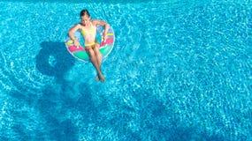 Η εναέρια άποψη του κοριτσιού στην πισίνα άνωθεν, παιδί κολυμπά διογκώσιμο doughnut δαχτυλιδιών στο νερό στις οικογενειακές διακο Στοκ Φωτογραφία