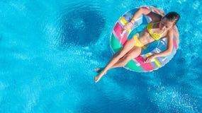 Η εναέρια άποψη του κοριτσιού στην πισίνα άνωθεν, παιδί κολυμπά διογκώσιμο doughnut δαχτυλιδιών στο νερό στις οικογενειακές διακο Στοκ εικόνα με δικαίωμα ελεύθερης χρήσης