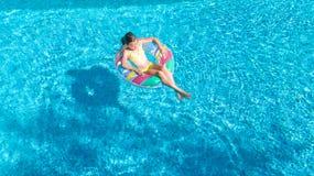 Η εναέρια άποψη του κοριτσιού στην πισίνα άνωθεν, παιδί κολυμπά διογκώσιμο doughnut δαχτυλιδιών στο νερό στις οικογενειακές διακο Στοκ φωτογραφία με δικαίωμα ελεύθερης χρήσης