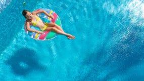 Η εναέρια άποψη του κοριτσιού στην πισίνα άνωθεν, παιδί κολυμπά διογκώσιμο doughnut δαχτυλιδιών στο νερό στις οικογενειακές διακο Στοκ Φωτογραφίες