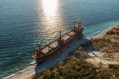 Η εναέρια άποψη του φορτηγού πλοίου τρέχει προσαραγμένο στην άγρια ακτή, ναυάγιο μετά από τη θύελλα στοκ εικόνα με δικαίωμα ελεύθερης χρήσης