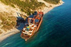 Η εναέρια άποψη του φορτηγού πλοίου τρέχει προσαραγμένο στην άγρια ακτή, ναυάγιο μετά από τη θύελλα στοκ φωτογραφίες