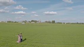 Η εναέρια άποψη το κορίτσι και ο τύπος πηγαίνει στον πράσινο τομέα απόθεμα βίντεο