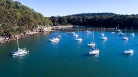 Η εναέρια άποψη των βαρκών έδεσε στον ποταμό Hawkesbury, Μπρούκλιν, Αυστραλία το μπλε νερό που περιβλήθηκε με από τα δέντρα γόμμα Στοκ Εικόνα