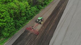 Η εναέρια έρευνα, τοπ άποψη, άνοιξη, καλλιεργητής τρακτέρ καλλιεργεί, σκάβει το χώμα το τρακτέρ οργώνει τον τομέα αυτοματοποιημέν φιλμ μικρού μήκους