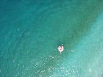 Η εναέρια νέα γυναίκα άποψης στο γίγαντα διόγκωσε το επιπλέον σώμα φλαμίγκο στο νερό turquois της ιόνιας θάλασσας Αλβανία στοκ φωτογραφία με δικαίωμα ελεύθερης χρήσης