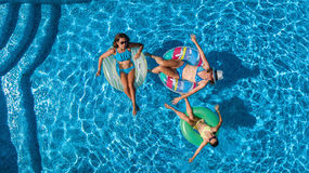 Η εναέρια τοπ άποψη της οικογένειας στην πισίνα άνωθεν, η ευτυχή μητέρα και τα παιδιά κολυμπούν στο διογκώσιμο δαχτυλίδι donuts κ Στοκ Φωτογραφία