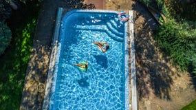 Η εναέρια τοπ άποψη των παιδιών στην πισίνα άνωθεν, ευτυχή παιδιά κολυμπά στο διογκώσιμο δαχτυλίδι donuts στο νερό στην οικογένει Στοκ Φωτογραφία