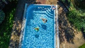 Η εναέρια τοπ άποψη των παιδιών στην πισίνα άνωθεν, ευτυχή παιδιά κολυμπά στο διογκώσιμο δαχτυλίδι donuts στο νερό στην οικογένει Στοκ Φωτογραφίες