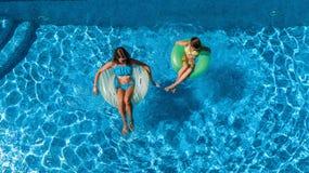 Η εναέρια τοπ άποψη των παιδιών στην πισίνα άνωθεν, ευτυχή παιδιά κολυμπά στο διογκώσιμο δαχτυλίδι donuts στο νερό στην οικογένει Στοκ Εικόνες