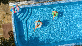 Η εναέρια τοπ άποψη των παιδιών στην πισίνα άνωθεν, ευτυχή παιδιά κολυμπά στο διογκώσιμο δαχτυλίδι donuts στο νερό στην οικογένει Στοκ εικόνες με δικαίωμα ελεύθερης χρήσης