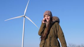 Η ενεργειακή παραγωγή από τον αέρα, ευτυχές κορίτσι μιλά τηλεφωνικώς εκτός από τις γεννήτριες αιολικής ενέργειας απόθεμα βίντεο