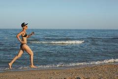 Η ενεργός φίλαθλη γυναίκα τρέχει κατά μήκος της ωκεάνιας κυματωγής από τη λίμνη νερού που κρατούν κατάλληλη και την υγεία Μαύρο υ στοκ εικόνα
