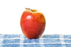Η ενιαία κόκκινη Apple σε μπλε Placemat Στοκ εικόνες με δικαίωμα ελεύθερης χρήσης