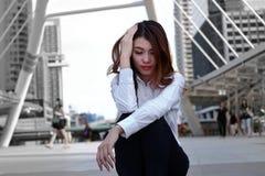 Η εξαντλημένη νέα ασιατική επιχειρηματίας με το χέρι στο συναίσθημα προσώπου κούρασε και ουδετεροποίηση με την εργασία του Ματαιω στοκ εικόνες