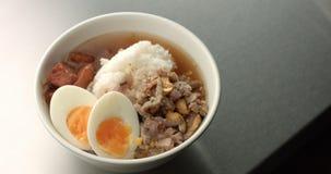 Η εξυπηρέτηση της ασιατικής σούπας ύφους με το ρύζι, χοιρινό κρέας, το αυγό και η μελιτζάνα Στοκ εικόνα με δικαίωμα ελεύθερης χρήσης
