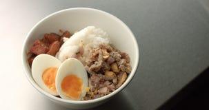 Η εξυπηρέτηση της ασιατικής σούπας ύφους με το ρύζι, χοιρινό κρέας, το αυγό και η μελιτζάνα Στοκ Εικόνες