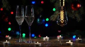 Η εορταστική ατμόσφαιρα δύο γυαλιά χύνει τη σαμπάνια στον πίνακα είναι αναμμένες λάμπες φωτός κίνηση αργή απόθεμα βίντεο
