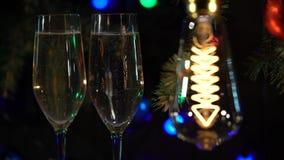 Η εορταστική γιρλάντα δύο ατμόσφαιρας σαμπάνια γυαλιών στον πίνακα είναι αναμμένες λάμπες φωτός απόθεμα βίντεο