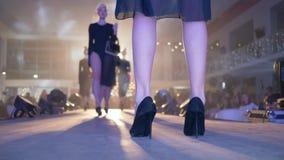 Η επίδειξη μόδας, όμορφα πόδια των προτύπων στα μαύρα ψηλοτάκουνα παπούτσια περπατά επάνω το στενό διάδρομο στη φωτεινή ελαφριά κ φιλμ μικρού μήκους