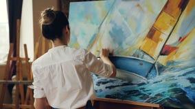 Η επαγγελματική γυναίκα ζωγράφος εργάζεται στην εικόνα χρησιμοποιώντας τα ελαιοχρώματα και το παλέτα-μαχαίρι δημιουργώντας όμορφο απόθεμα βίντεο