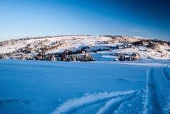 Η επαρχία χειμερινών βουνών με τη διασκορπισμένη τακτοποίηση, ο λόφος με τα λιβάδια και τα δέντρα, το χιόνι και ο σαφής ουρανός κ Στοκ Φωτογραφίες