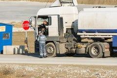 Η επαλήθευση των εγγράφων από το φορτηγό δεξαμενών οδηγών στο σημείο ελέγχου ασφάλειας στο vezde προστατεύει Στοκ φωτογραφία με δικαίωμα ελεύθερης χρήσης