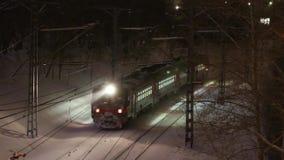 Η επιβατική αμαξοστοιχία πηγαίνει στον τρόπο railbridge κάτω τη νύχτα κατά τη διάρκεια των χιονοπτώσεων απόθεμα βίντεο
