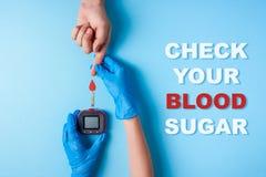 Η επιγραφή ελέγχει τη ζάχαρη και τη νοσοκόμα αίματός σας που κάνουν ένα χέρι ατόμων ` s εξετάσεων αίματος με το κόκκινο αίμα να μ στοκ φωτογραφία