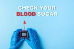 Η επιγραφή ελέγχει τη ζάχαρη και τη νοσοκόμα αίματός σας που κάνουν μια εξέταση αίματος με το κόκκινο αίμα να μειωθεί και το μετρ στοκ φωτογραφία