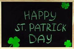 Η επιγραφή με την πράσινη κιμωλία σε έναν πίνακα κιμωλίας: Ευτυχής ημέρα του ST Πάτρικ φύλλα τριφυλλιού Στοκ Φωτογραφία