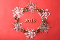 Η επιγραφή 2019 σε ένα πλαίσιο snowflakes και του ντεκόρ Χριστουγέννων σε ένα κόκκινο υπόβαθρο επάνω από την όψη στοκ εικόνα