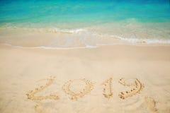 Η επιγραφή στην άμμο, γιορτάζει το νέο έτος στους τροπικούς κύκλους νέο έτος διακοπών Στοκ Εικόνες