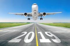 Η επιγραφή στην επιφάνεια διαδρόμων 2019 της σύστασης διαδρόμων αερολιμένων με το αεροπλάνο απογείωσης Έννοια του ταξιδιού στο νέ στοκ εικόνες