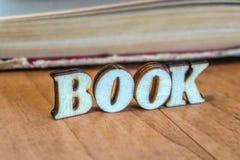 Η επιγραφή των ξύλινων επιστολών στο υπόβαθρο ενός παλαιού βιβλίου στοκ εικόνες με δικαίωμα ελεύθερης χρήσης