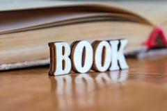 Η επιγραφή των ξύλινων επιστολών στο υπόβαθρο ενός παλαιού βιβλίου στοκ φωτογραφία