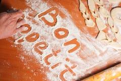 Η επιγραφή bon appetit στον πίνακα με το αλεύρι Στοκ Φωτογραφία