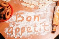 Η επιγραφή bon appetit στον πίνακα με το αλεύρι Στοκ εικόνες με δικαίωμα ελεύθερης χρήσης
