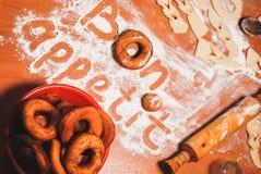 Η επιγραφή bon appetit στον πίνακα με το αλεύρι Στοκ Φωτογραφίες