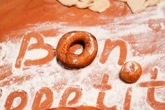 Η επιγραφή bon appetit στον πίνακα με το αλεύρι Στοκ φωτογραφία με δικαίωμα ελεύθερης χρήσης