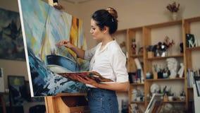 Η επιδέξια γυναίκα ζωγράφος εργάζεται στη μόνη εικόνα ζωγραφικής στούντιο easel χρησιμοποιώντας τα ελαιοχρώματα, την παλέτα και τ απόθεμα βίντεο