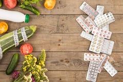 η επιλογή μεταξύ του υγιούς τρόπου ζωής και των φαρμάκων, των λαχανικών ή των χαπιών στο καφετί ξύλινο γραφείο Στοκ φωτογραφία με δικαίωμα ελεύθερης χρήσης