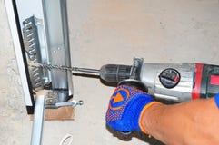 Η επισκευή αναδόχου και εγκαθιστά την πόρτα γκαράζ με τη μηχανή διατρήσεων Αντικαταστήστε μια σπασμένη άνοιξη πορτών γκαράζ Στοκ φωτογραφία με δικαίωμα ελεύθερης χρήσης