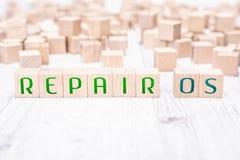 Η επισκευή OS λέξεων που διαμορφώνεται από τους ξύλινους φραγμούς σε έναν άσπρο πίνακα στοκ εικόνες