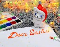 Η επιστολή σε Santa με τα χρώματα, φω'τα μιας γιρλάντας στο υπόβαθρο, δίπλα σε τον είναι χρώματα και ένα παιχνίδι μιας γάτας στοκ φωτογραφίες